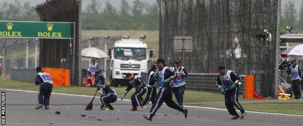 Stewards sweep up debris at the Chinese Grand Prix