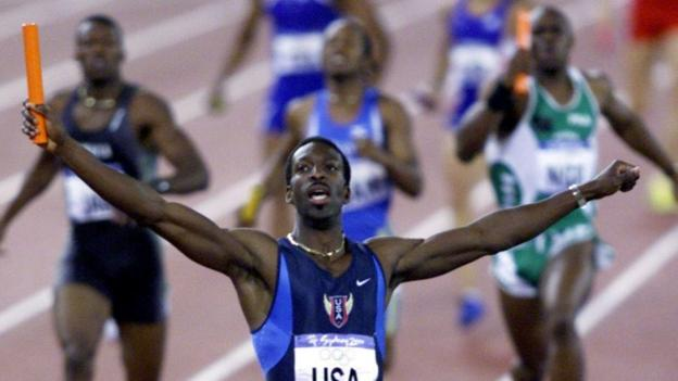 Michael Johnson celebrates winning the men's 4x400m relay with Team USA