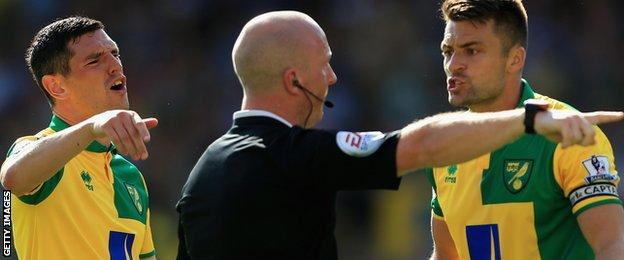 Norwich players remonstrate with referee Simon Hooper