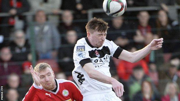 Billy Joe Burns wins an aerial duel with Cliftonville's Chris Curran in Tuesday's game