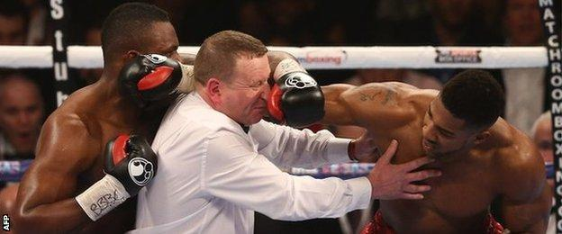 Referee Howard Foster tries to separate Dillian Whyte and Anthony Joshua