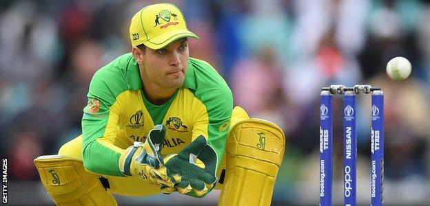 Australia wicketkeeper Alex Carey bends low to catch a ball against Sri Lanka