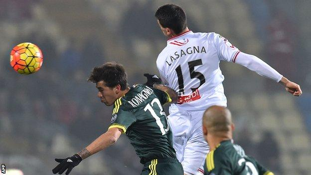 AC Milan defender Alessio Romagnoli (left) jumps for the ball with Carpi's Kevin Lasagna