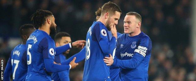 Gylfi Sigurdsson looks downcast while his Everton team-mates celebrate around him after his goal against former club Swansea City