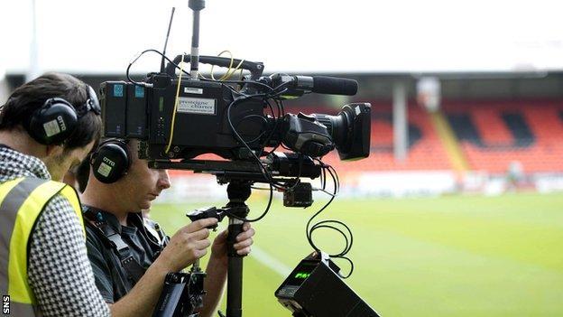 A television cameraman prepares to shoot a football match