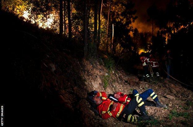 Οι πυροσβέστες ξεκουράζονται κατά τη διάρκεια μιας πυρκαγιάς στην κεντρική Πορτογαλία τον Ιούνιο του 2017