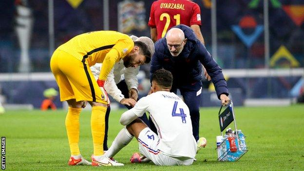 Raphael Varane sits on the grass after picking up an injury during France's Nations League final win against Spain
