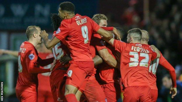 James Berrett is mobbed by his teammates after scoring what proved to be the winner