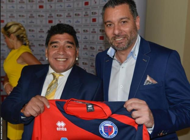 Football legend Diego Maradona holds a Biggleswade United shirt with the club's chairman Guillem Balague