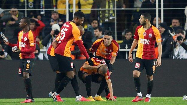 Galatasaray players take shelter from objects being thrown onto the Fenerbahce pitch