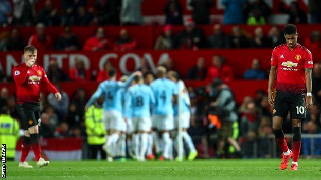 Man City players celebrate as Luke Shaw (left) and Marcus Rashford (right) look crestfallen
