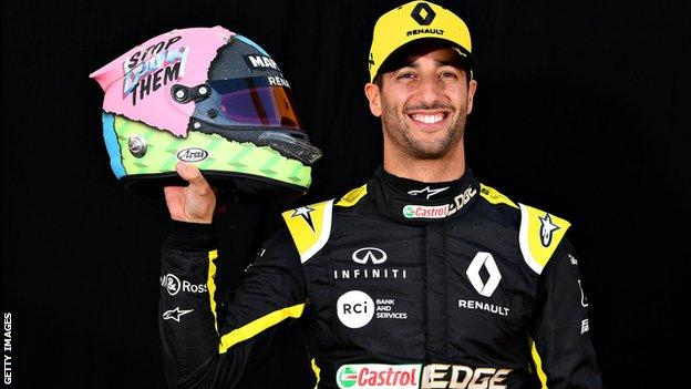 Daniel Ricciardo holds up his new helmet design