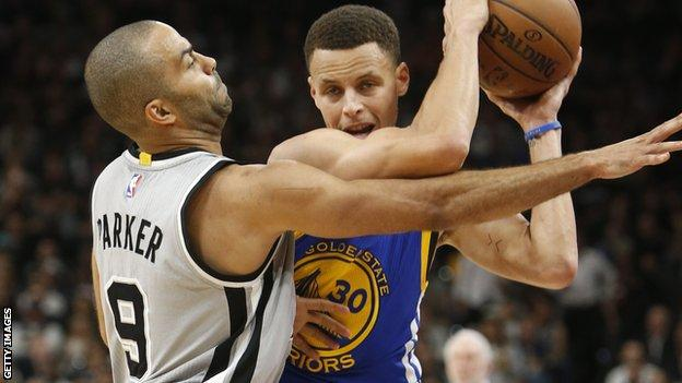 Stephen Curry (right) guarded by Spurs' Tom Parker