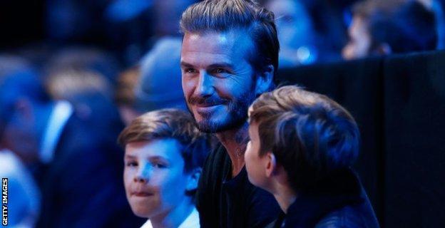David Beckham (C) and his sons, Cruz (L) and Romeo (R) attend the men's singles semi final between Rafael Nadal of Spain and Novak Djokovic