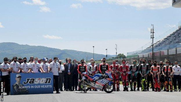 Riders and support staff observe a minute of silence in tribute to Dupasquier