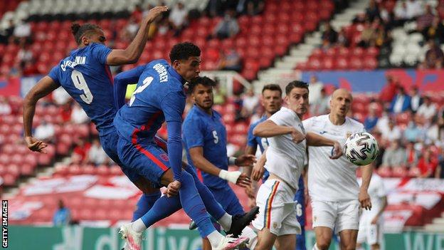 England's Dominic Calvert-Lewin and Ben Godfrey get up for a header in the box against Romania
