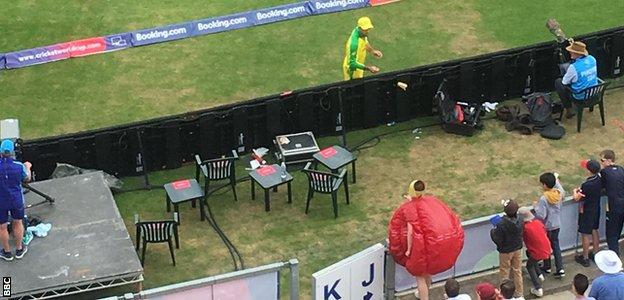 One spectator, dressed as a cricket ball, throws sandpaper at Glenn Maxwell during England's innings