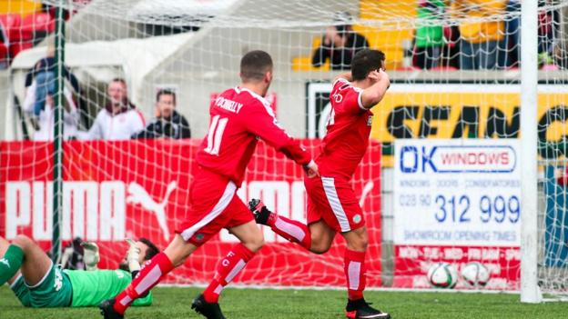 Reds striker David McDaid runs away in delight after his goal gives the Solitude hosts a 1-0 victory over the Glens