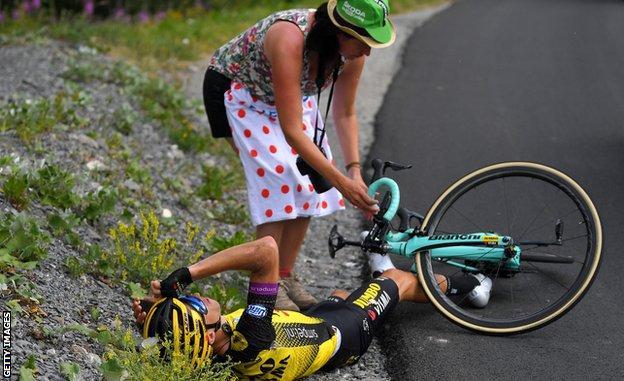 A Tour de France fan heps a stricken rider