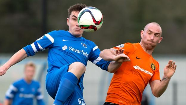 James McKenna of Ballinamallard in aerial action with Carrick Rangers midfielder Barry Johnston at Ferney Park
