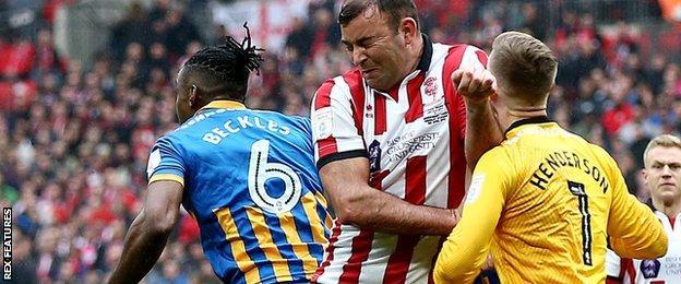 Lincoln's Matt Rhead collides with Shrewsbury goalkeeper Dean Henderson