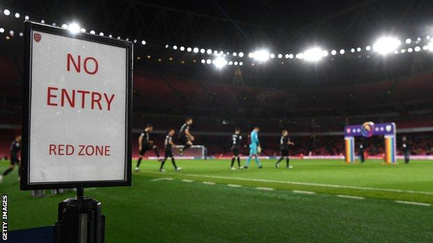 Players enter the field of play at the Emirates Stadium with a red zone sign on display