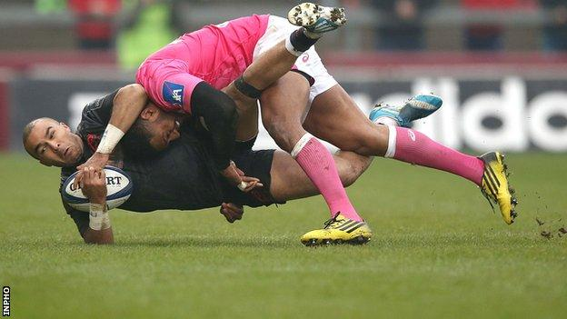 Munster's Simon Zebo is tackled by Stade Francais's Julien Arias at Thomond Park