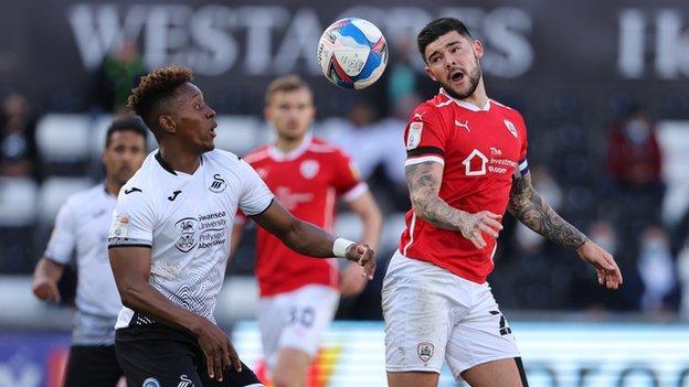 Barnsley's Alex Mowatt battles with Swansea's Jamal Lowe