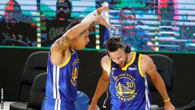 Curry is soaked by fellow Warriors player Juan Toscano-Anderson after the win