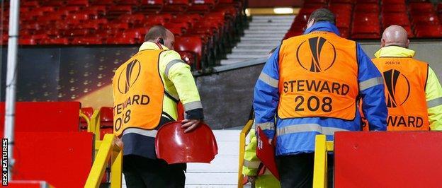 A broken seat is held by a steward