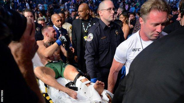 Conor McGregor leaves the octagon on a stretcher