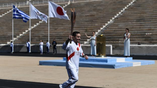 An athlete carries the Olympic flame