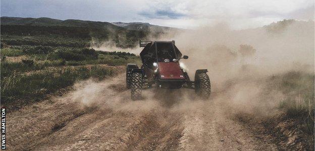 Lewis Hamilton riding a dune buggy