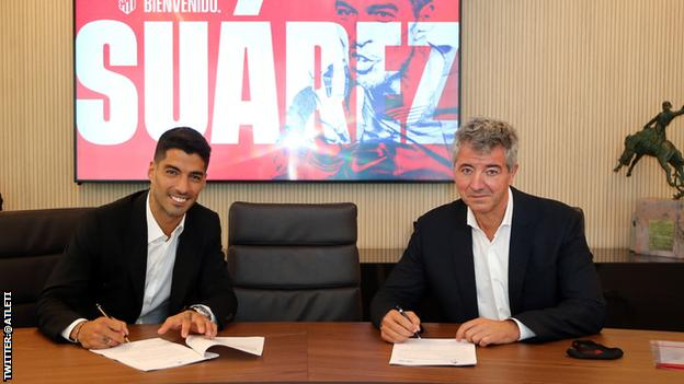 Luis Suarez signing his contract to join Atletico Madrid