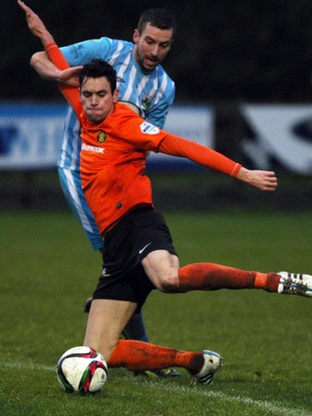 Mark Surgenor of Carrick Rangers gets the ball away under pressure from Warrenpoint Town opponent Stephen Murray during the 1-1 draw at Milltown
