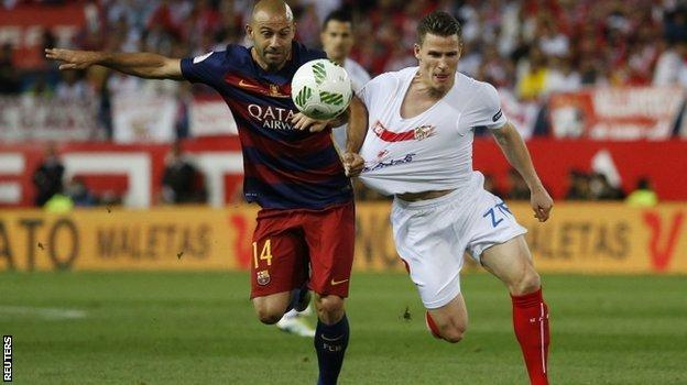 Javier Mascherano of Barcelona and Kevin Gameiro of Sevilla