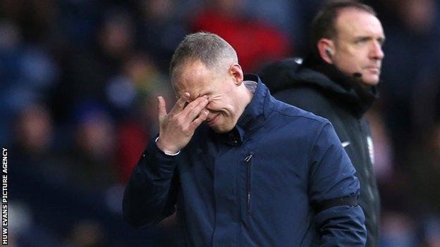 Steve Cooper rubs his eyes in despair during Swansea' heavy defeat at the Hawthorns