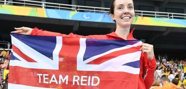 Long jumper Stef Reid holding a 'Team Reid' flag at the Rio Paralympics