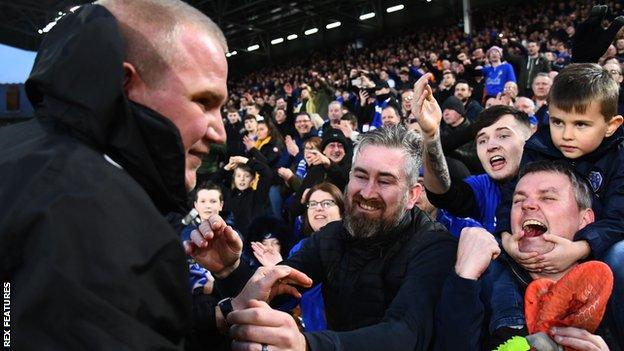 Pete Wild celebrates with Oldham's fans after their FA Cup win against Fulham at craven Cottage
