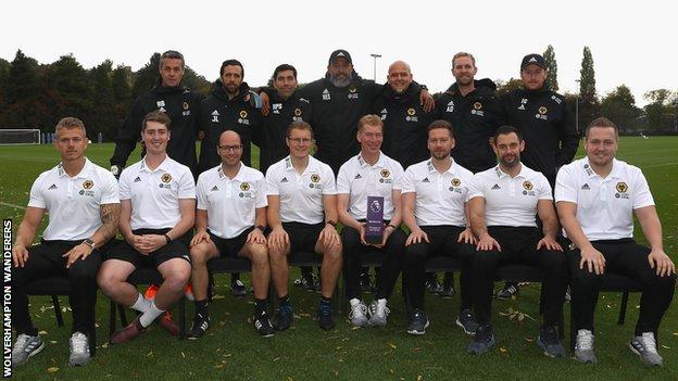 Nuno Espirito Santo poses with 14 members of his backroom staff after receiving September's manager of the month award