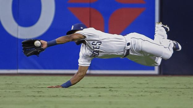 San Diego, United States, 13 August: Manuel Margot of the San Diego Padres takes a diving catch against the Los Angeles Angels. (Photo by Denis Poroy/Getty Images)