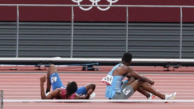 Botswana's Nijel Amos (right) and USA's Isaiah Jewett sit on the track after falling during the semi-finals of the men's Olympic 800m