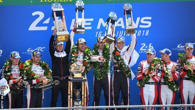 Toyota TS050 Hybrid LMP1's drivers Fernando Alonso of Spain (L), Kazuki Nakajima of Japan (R) and Sebastien Buemi of Switzerland (C), celebrate on the podium after winning