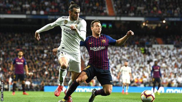 Real Madrid forward Gareth Bale (left) in action against Barcelona