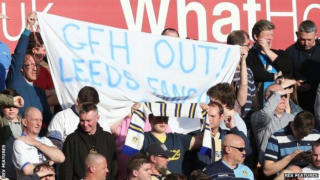 """Leeds fans hold a banner reading """"GFH out! Leeds fans in"""""""