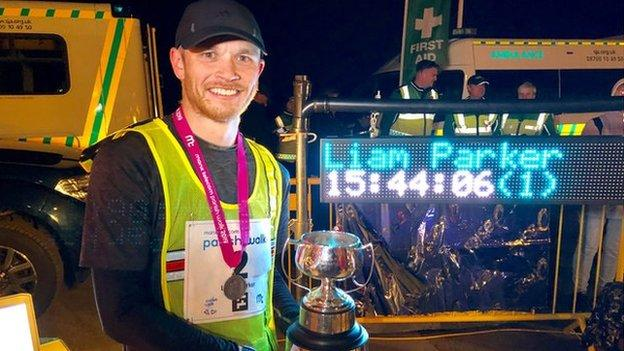 2019 Parish Walk winner Liam Parker holding the trophy with his finishing time on a screen behind