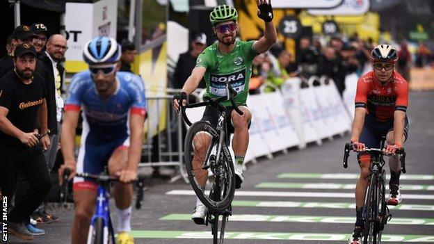 Peter Sagan (in green) pulling a wheelie across the finish line on stage 20