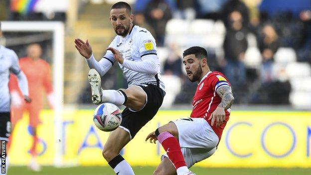 Swansea's Conor Hourihane challenges Barnsley's Alex Mowatt