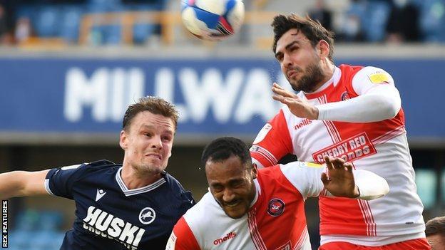 Millwall striker Matt Smith challenges Jordan Obita and Ryan Tafazolli for the ball