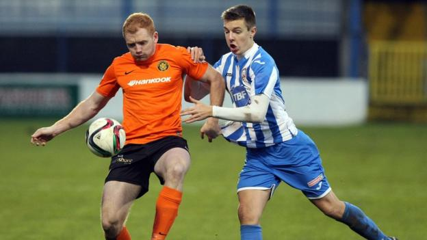 Joe McNeill tries to keep possession for Carrick Rangers as Coleraine's Brad Lyons prepares to put in a challenge